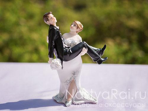 Фигурка невеста держит на руках жениха